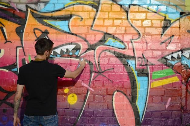 Young graffiti artist with backpack and gas mask on his neck paints colorful graffiti in pink tones on brick wall