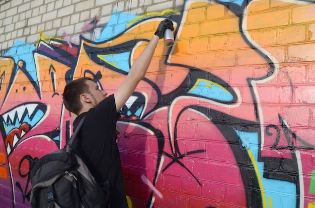 Young graffiti artist with backpack and gas mask on his neck paints colorful graffiti
