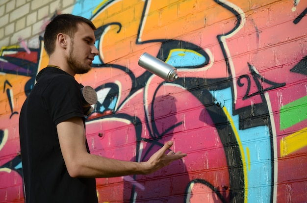 그의 목에 가스 마스크와 젊은 낙서 예술가 그의 스프레이 던져 벽돌 벽에 화려한 핑크 낙서에 대 한 수 있습니다. 거리 예술과 현대 회화 과정