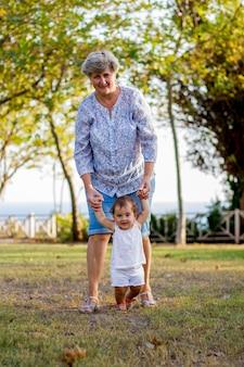 녹색 공원에서 그녀의 손녀와 함께 산책에 젊은 할머니와 할아버지