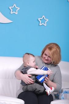 Молодая бабушка с маленьким внуком на белом диване. синяя стена с белой луной и звездами на стене.