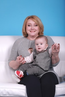 Young grandmother with her little grandson on a white sofa, blue wall with a white moon and stars on a wall.