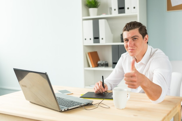 Young graphic designer man in white shirt gesture thumb up