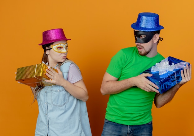Young greedy couple wearing pink and blue hats put on masquerade eye masks holds gift boxes looking at each other isolated on orange wall