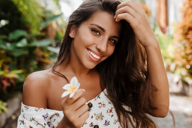 Young green-eyed lady with tattoo on her arm is smiling and posing with white flower in garden