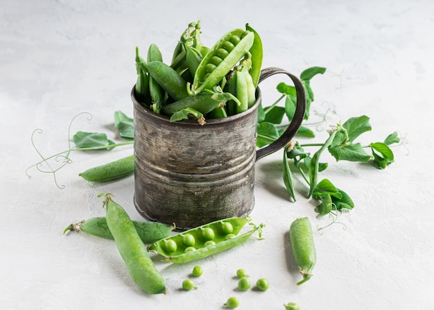 Young green peas pods in a metal cup