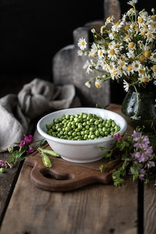 Young green peas in white bowl on wooden. pea flowers and daisy flowers on the table.