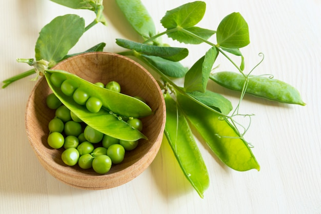 Young green peas on white wooden surface
