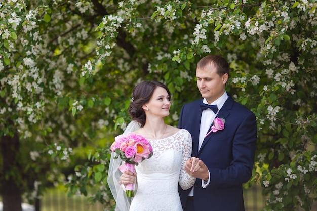 咲く庭でピンクのウェディングブーケと若い新郎新婦