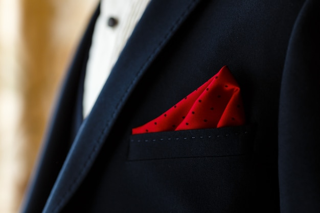 Young groom in dark blue suit with red dotted handkerchief in the pocket