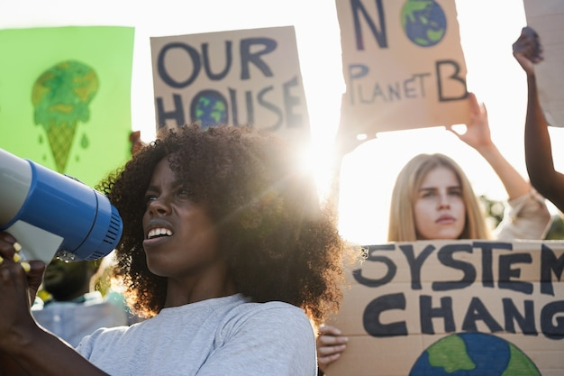 Young group of demonstrators on road from different culture and race protest for climate change - focus on african girl face