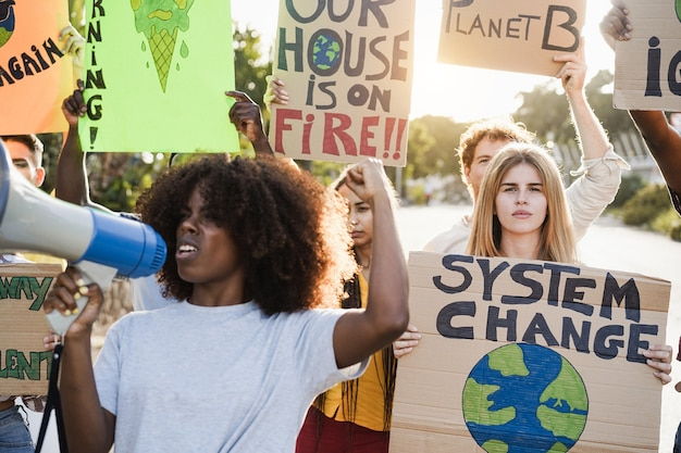 Young group of demonstrators on road from different culture and race protest for climate change - focus on right girl face