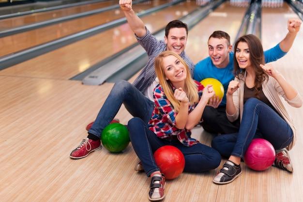 Giovane gruppo di amici in pista da bowling