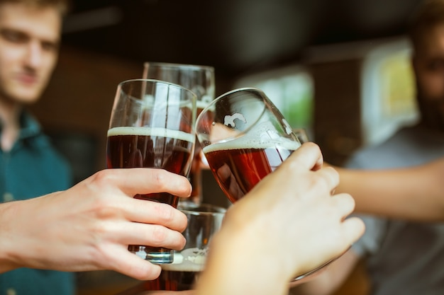 友達の若いグループがビールのボトルをチリンと鳴らし、楽しんで、一緒に祝っています。