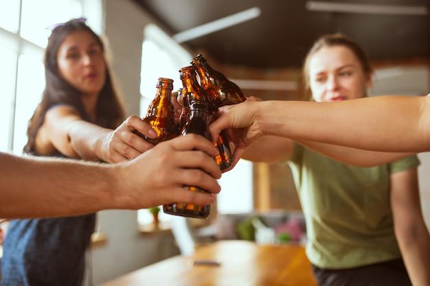 Молодая группа друзей пьет пиво, весело смеется и празднует вместе крупным планом звон