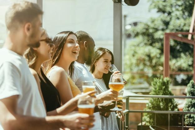 Молодая группа друзей пьет пиво, веселится, смеется и празднует вместе. женщины и мужчины с бокалами пива в солнечный день. октоберфест, дружба, единение, счастье, летняя концепция.