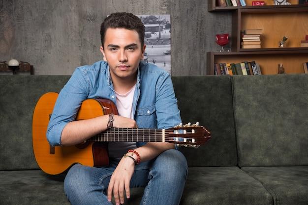 美しいギターを持ってソファに座っている若いギタリスト。高品質の写真