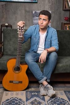 Giovane chitarrista che tiene una bella chitarra e che si siede sul sofà. foto di alta qualità