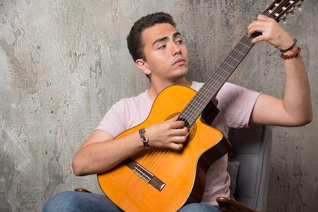Молодой гитарист держит гитару на мраморном фоне