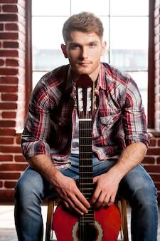 젊은 기타리스트. 어쿠스틱 기타에 턱을 기대고 의자에 앉아 카메라를 바라보는 잘생긴 청년
