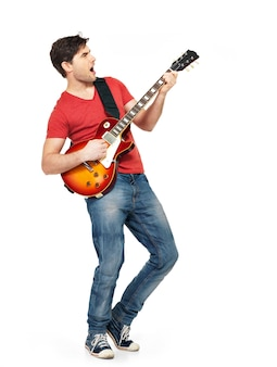 Young guitarist plays on the electric guitar with bright emotions, isolatade on white background
