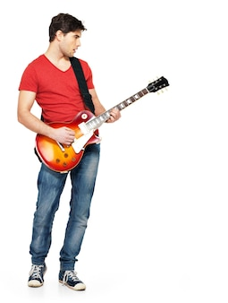 Young guitarist plays on electric guitar with bright emotions, isolate on white