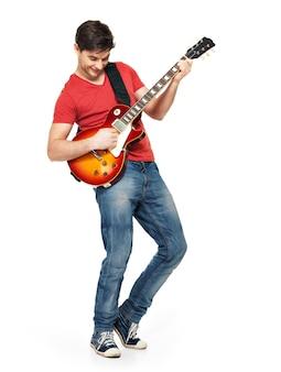 Молодой гитарист играет на электрогитаре с яркими эмоциями, изолирован на белой стене