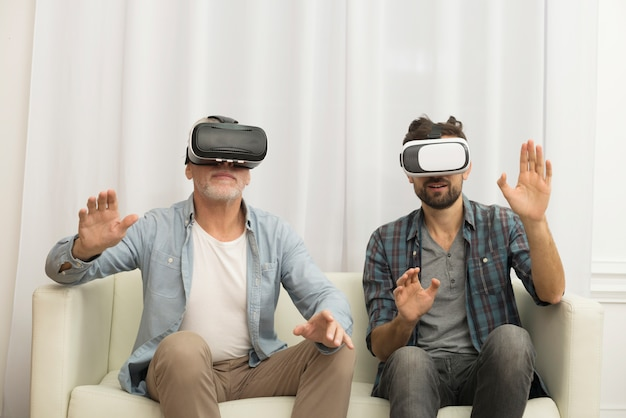 Young guy and aged man with vr glasses on settee