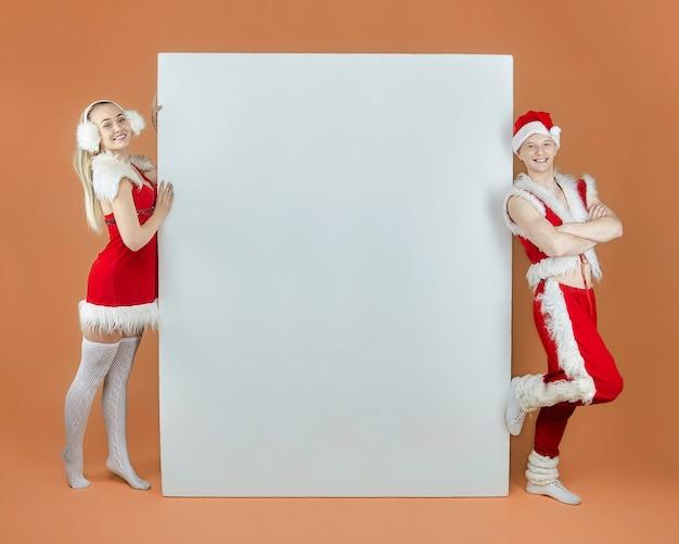 広告レイアウトのサンタクロースの衣装を着た若い男と少女。クリスマスと新年のコンセプト