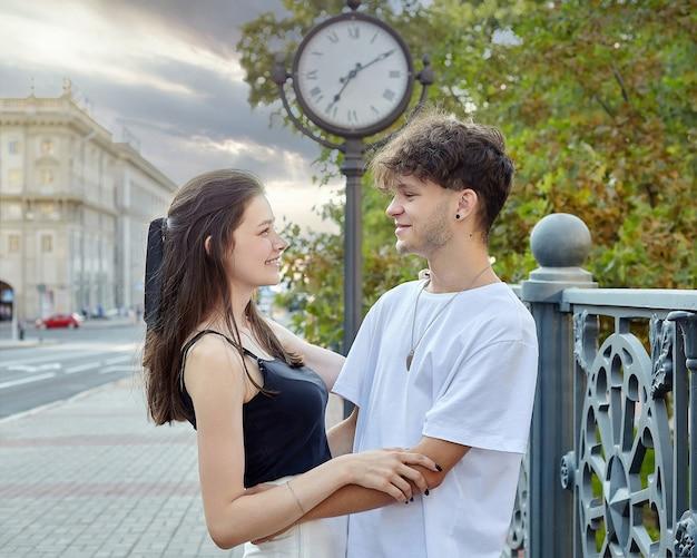 若い男と少女は、大きな時計を背景にお互いを見つめています。