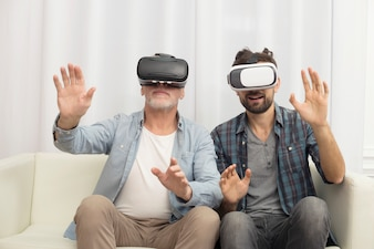 Young guy and aged man with VR glasses on sofa