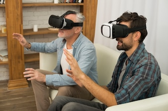 Young guy and aged man with VR glasses sitting on settee