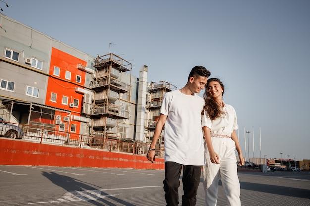 젊은 남자와 여자는 따뜻한 날에 도시 건물의 배경에 광장을 걷고 있습니다.