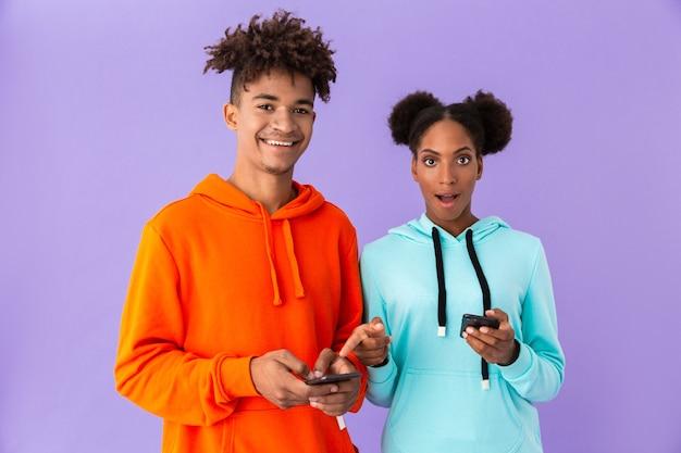 紫色の壁に隔離されたスマートフォンを使用して若い男と女