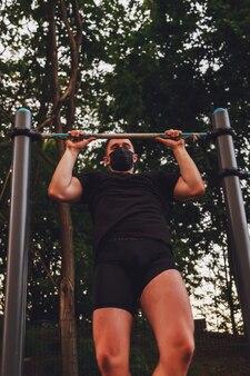 Молодой парень, спортсмен тянет за штангу. он в черной медицинской маске