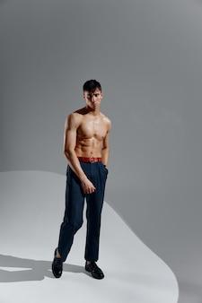 ポンプアップされた胴体ボディービルダーフィットネスグレーの背景ジーンズ靴モデルを持つ若い男のアスリート