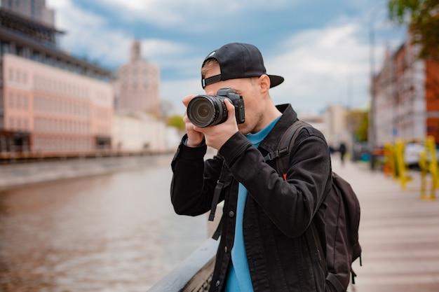 젊은 남자 검은 모자, 카메라 센터 대도시 도시 남자 사진을 찍습니다. 여행하는 동안 휴가의 순간을 포착하세요.