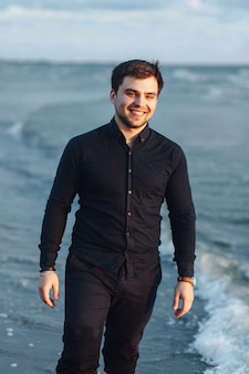 A young guy in a black shirt walks along the seashore in the evening