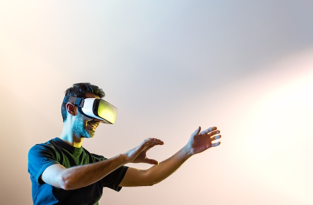 Young guy in black tshirt with virtual reality glasses and raised hands looking to the right illuminated with yellow and blue lights with pinkish background and copy space