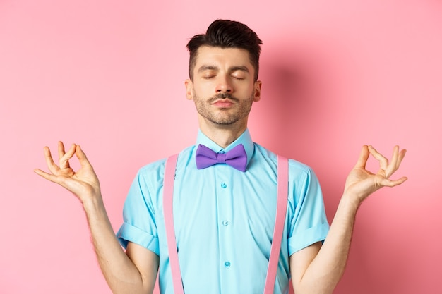 Young guy in bow-tie standing calm and peaceful, meditating with hands in mudra zen gesture and closed eyes, practice yoga to relax, standing over pink background.