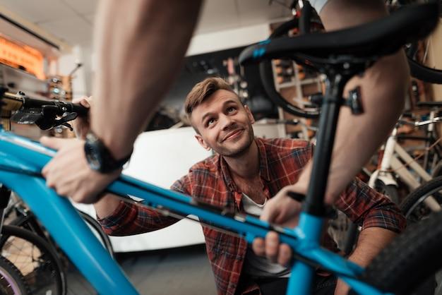 Young guy bring bicycle to repair in workshop.