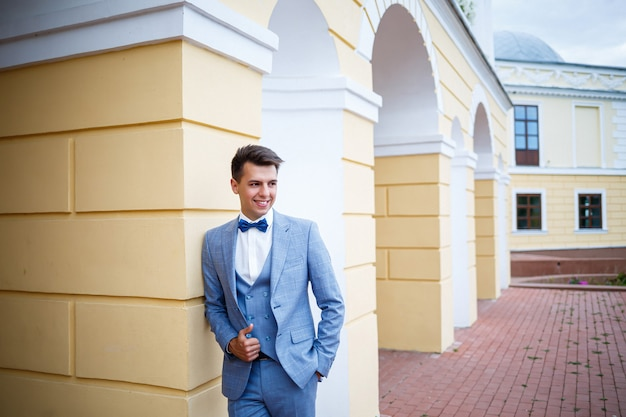 彼らの結婚式の日に若い男のビジネスマンの新郎、スタイリッシュな服、公園の散歩