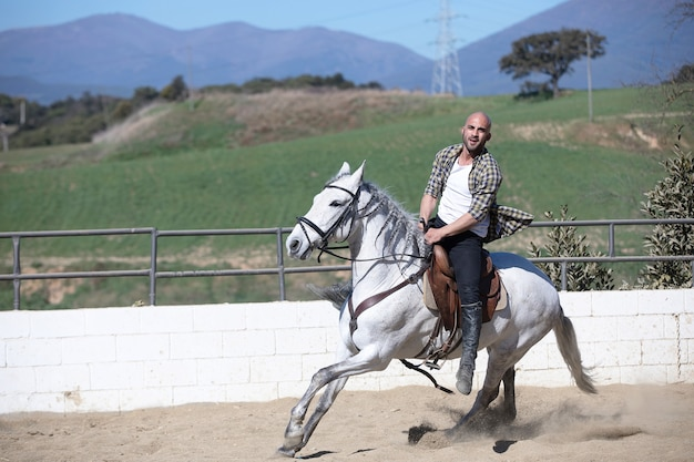 Young guy in casual outfit riding white horse on sandy ground