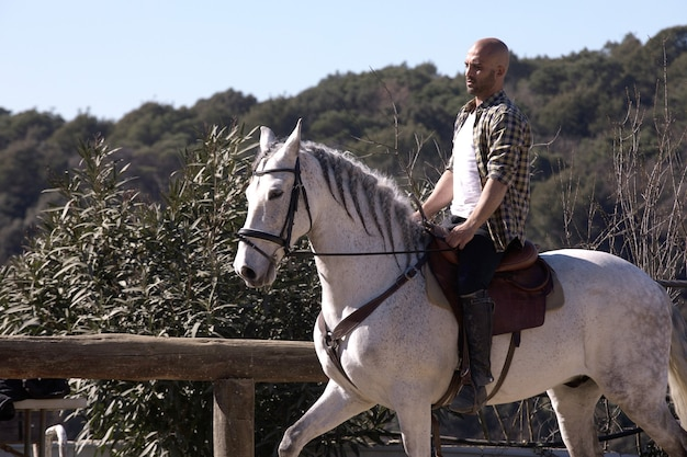 Young guy in casual outfit riding white horse