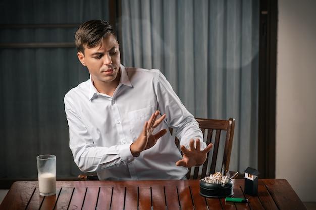 若い男は健康的なライフスタイルを選択し、禁止を示し、タバコのパック、タバコで満たされた灰皿を指しています。反タバコの概念。
