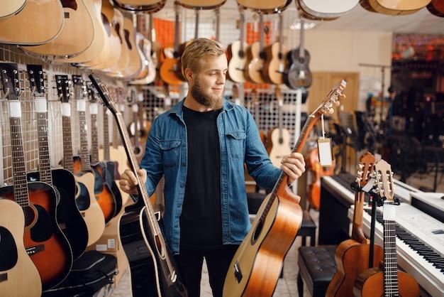 ミュージックストアでアコースティックギターを選ぶ若い男