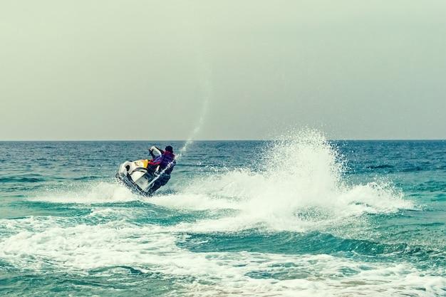 ジェットスキーで大西洋をクルージングする若い男。アクアバイク大会での海水でのアクティブなレジャー。海でのウォーターエンターテインメント。海での夏の観光休暇。