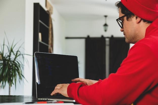 집에서 컴퓨터로 작업하는 빨간 옷을 입은 젊은 남자 개발자