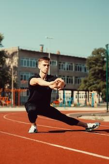 Молодой парень делает разминку перед спортивными упражнениями на школьном стадионе