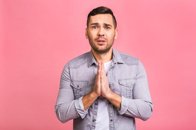若い男は、祈りや瞑想で両手を合わせて、カジュアルな服装をしました Premium写真